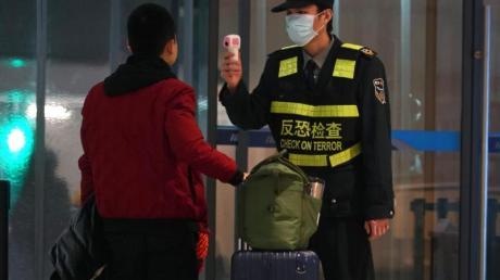 Schutzmaßnahme gegen die Verbreitung des Corona-Virus: Ein Beamter misst am Flughafen von Wuhan die Körpertemperatur von Reisenden.