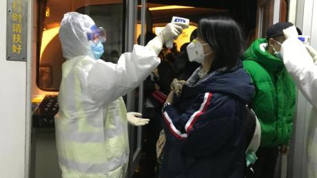 Gesundheitsbeamte kontrollieren in Peking die Körpertemperatur aus Wuhan angereister Passagiere.