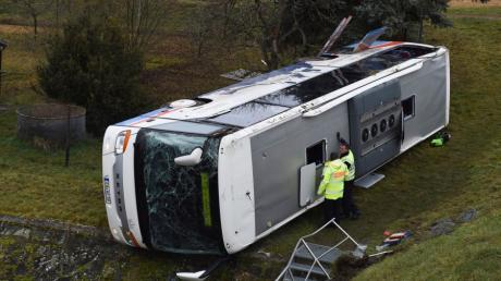 Polizisten stehen an einem verunglückten Schulbus, der am Morgen bei Eisenach in Thüringen auf eisglatter Straße verunglückte.