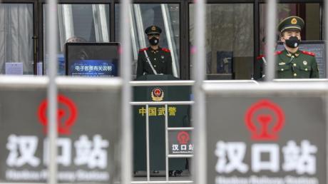 Sicherheitskräfte stehen mit Mundschutz vor dem geschlossenen Bahnhof Hankou in Wuhan.