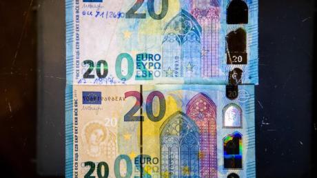 Fälschung und Original: Um einen echten Geldschein (unten) von einer nachgemachten Banknote (oben) unterscheiden zu können, sollten Bankkunden auf die Sicherheitsmerkmale achten.