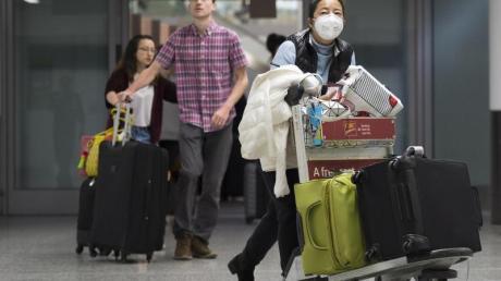 Eine Frau trägt am Toronto Pearson International Airport eine Atemschutz-Maske. Immer mehr Länder prüfen eine Evakuierung ihrer Landsleute.