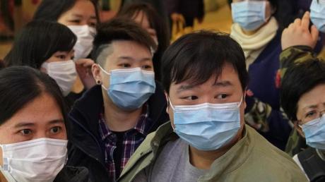 Menschen warten vor einem Geschäft in Hongkong, um Atemschutzmasken zu kaufen.