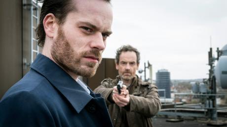 """Peter Faber (Jörg Hartmann) hat seine Waffe auf Markus Graf (Florian Bartholomäi) gerichtet. Szene aus dem Dortmund-Tatort """"Monster"""", der heute im Ersten läuft."""