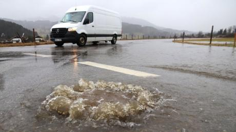 Wasser quillt aus einem Kanal an einer  teilweise überfluteten Straße. Aufgrund vonstarken Regenfällen wird in Bayern gebietsweise Hochwasser erwartet.