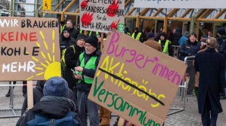 Klimaaktivisten demonstrieren mit Plakaten vor der Olympiahalle in München, wo die Siemens-Hauptversammlung stattfindet.