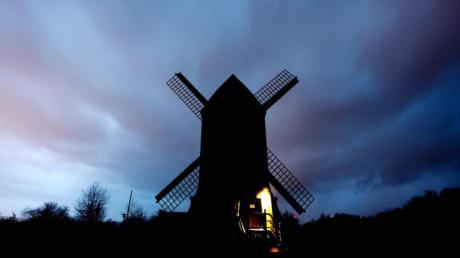 """Eine schwarze Mühle steht am Horizont, während das Sturmtief """"Sabine"""" über die Paltrockmühle Asel im Landkreis Hildesheim hinwegwegt."""