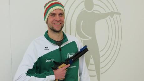 """Daniel Wrigley von der SG Ottmaring mit zwei seiner """"Markenzeichen"""": Mit der Luftpistole und der gestrickten Mütze in den Farben des FC Augsburg, zu dessen begeisterten Fans der 32-Jährige zählt."""