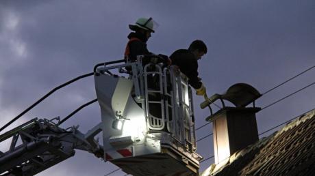 Kaminbrand in einem Einfamilienhaus in Buch. Der Kaminkehrer wurde von der Feuerwehr mit der Drehleiter auf das Dach gebracht.