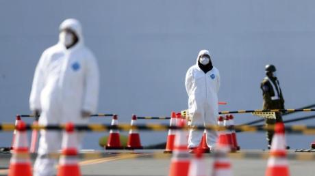 """Sicherheitskräfte stehen vor der """"Diamond Princess"""". Das Schiff hatte wegen des neuartigen Coronavirus zwei Wochen lang im japanischen Yokohama unter Quarantäne gestanden."""
