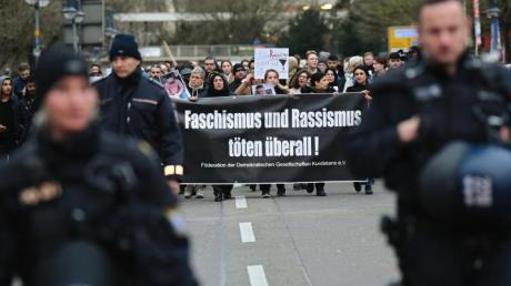 Zahlreiche Menschen laufen in Hanau während eines Trauermarsches vom Tatort Heumarkt zum Tatort Kurt-Schumacher-Platz.