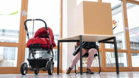 Eine Frau gibt in einer Wahlkabine in Hamburg ihre Stimme zur Bürgerschaftswahl ab, neben ihr steht ein Kinderwagen.