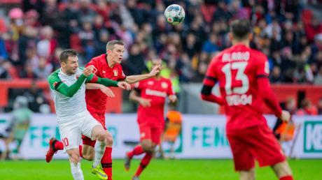 Leverkusens Sven Bender (r) und Augsburgs Daniel Baier versuchen an den Ball zu kommen.