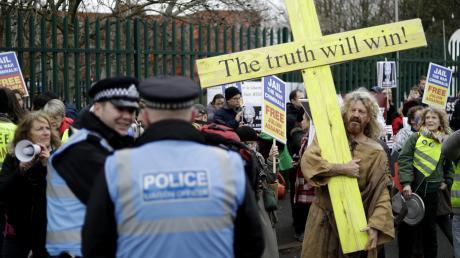 """Für seine Anhänger ist Julian Assange ein Märtyrer, der für die Freiheit kämpft. """"Die Wahrheit wird siegen"""" steht auf einem Holzkreuz, mit dem sich ein Unterstützer vor dem Gericht postiert hat, in dem die Anhörung stattfindet."""