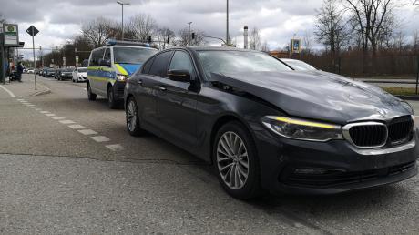 Ein schwarzer BMW mit verbeulter Front steht an der Unfallstelle in der Bürgermeister-Ackermann-Straße. Dahinter parkt ein Polizei-Fahrzeug.