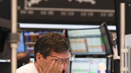 Ein Aktienhändler reibt sich auf dem Parkett der Frankfurter Börse die Augen.
