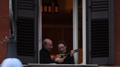 """In Rom nehmen ein Mann und eine Frau mit ihrer Mandoline am """"Flashmob sonoro"""" teil. Millionen Italiener müssen wegen des neuartigen Coronavirus zuhause bleiben."""