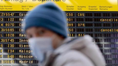 Ein Mann mit Mundschutz steht am Flughafen Berlin-Tegel vor der Anzeigetafel der Abflüge.