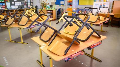 Stühle stehen in einer Grundschule in Stuttgart nach Ende der letzten Unterrichtsstunde auf den Tischen.