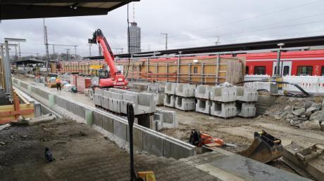 Am Augsburger Hauptbahnhof geht es voran: Unterhalb der Bahngleise wird der Tunnel gegraben. Der Bagger am Bahngleis hievt das Baumaterial auf den Wagen, um es abzutransportieren.