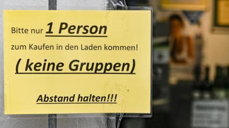 Ein Schild regelt den Einlass in ein Geschäft in Hamburg.