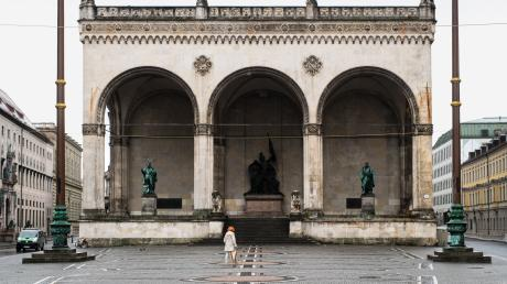 Eine Frau geht über den menschenleeren Odeonsplatz in München an der Feldherrnhalle vorüber.