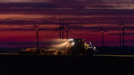 Ein Landwirt bearbeitet ein Feld bei rotem Abendhimmel. Den ersten dämmert's schon: Die Coronakrise kann auch eine Chance für die Landwirtschaft sein.