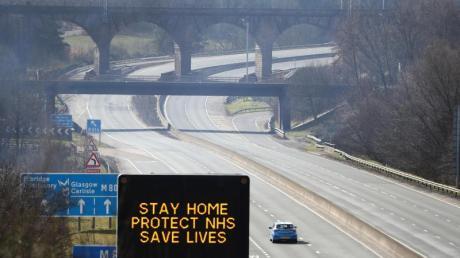 Eine digitale Anzeigentafel an einer Autobahn appelliert an die Fahrer, möglichst zu Hause zu bleiben.