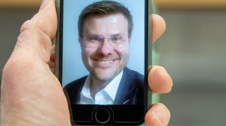 Marcus König, CSU-Spitzenkandidat für das Oberbürgermeisteramt in Nürnberg, lächelt per Video-Anruf nach den Ergebnissen der Auszählungen der Stichwahlen in die Kamera.