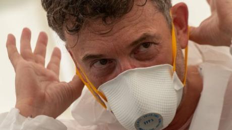 27.03.2020, Bayern, Aichach: Friedrich Pürner, Leiter des Gesundheitsamtes, demonstriert an der Coronastation das richtige Ablegen einer Atemschutzmaske. Hierbei sollte man jeden Kontakt mit der Frontseite der Maske vermeiden. Auf dem Gelände der Jugendverkehrsschule wurde eine Teststation eingerichtet, in der ab dem 28.03.2020 Angehörige systemrelevanter Berufe auf Ladung des Gesundheitsamtes getestet werden. Foto: Stefan Puchner/dpa +++ dpa-Bildfunk +++