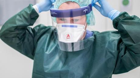 Die Stationsleiterin einer Infektionsstation beim Anlegen ihrer Schutzkleidung.