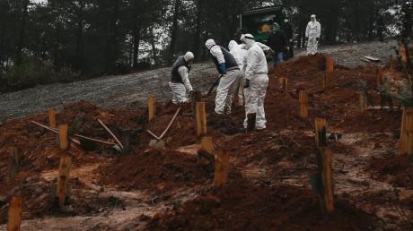 Gesundheitsbeamte heben in Istanbul Gräber auf einem neu angelegten Friedhof aus, den die Behörden für die Beerdigung der an Covid-19-Verstorbenen vorgesehen haben.