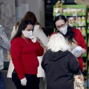 Mitarbeiterinnen eines Supermarktes in Wien verteilen am Eingang Mundschutzmasken an die Kunden.