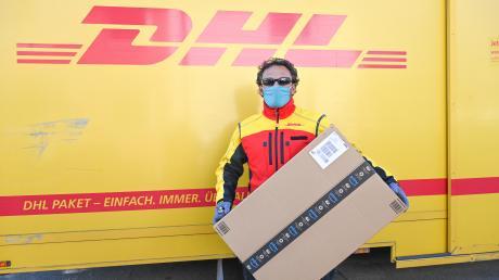 Ein Paketbote mit einer Schutzmaske. Bei DHL können Kunden die Pakete empfangen, ohne selbst unterschreiben zu müssen.