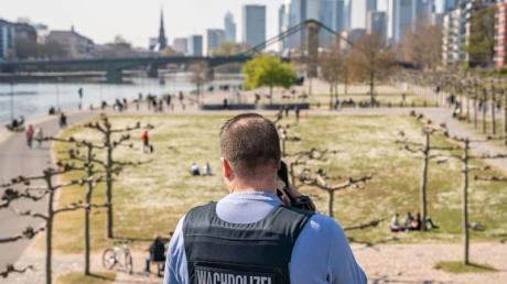 Ein Wachpolizist überprüft die Einhaltung der Kontaktsperre am Frankfurter Mainufer.