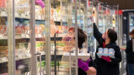 Mitarbeiterinnen in einem Supermarkt tragen Schutzmasken, während sie die Kühlregale mit Waren bestücken.