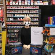 Eine Mitarbeiterin eines Geschäfts steht mit Atemschutzmaske und Handschuhen im Laden.