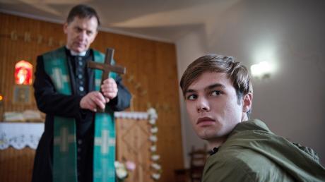 """Jonas Fleischauer (Tom Gronau) muss sich regelmäßig von Pater Anselm (Maciej Robakiewicz) exorzieren lassen: Szene aus dem """"Polizeiruf 110: Heilig sollt ihr sein""""."""