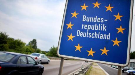 Autos passieren die Grenze zur Bundesrepublik.