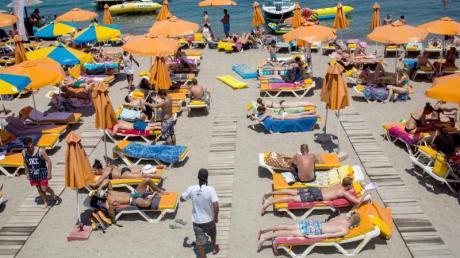 Touristen genießen die Sonne an einem Strand auf der griechischen Insel Kos. Die Hoffnung auf Grenzöffnungen für den Sommerurlaub wächst von Tag zu Tag.