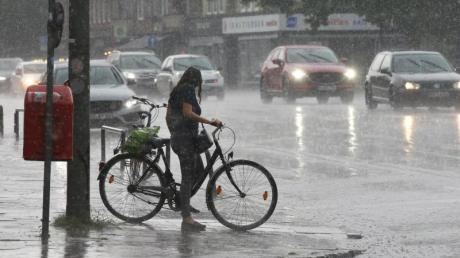 Eine Radfahrerin im strömendem Regen im Hamburger Stadtteil Wandsbek.