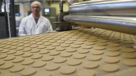 Kekse liegen bei einer Werksführung in der Printen-und Schokoladenfabrik Henry Lambertz GmbH & Co. KG auf einem Band. Die US-Strafzölle belasten auch die Deutsche Süßwarenindustrie.