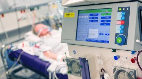 Ein Corona-Patient mit schwerem Verlauf auf der Intensivstation. Während in einigen Ländern Massengräber ausgehoben werden müssen, hält das Gesundheitssystem in Deutschland der Pandemie stand.