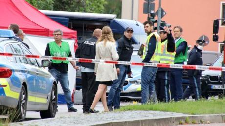 Polizisten steht am Tatort, an dem zuvor ein Mann auf der Straße getötet wurde.