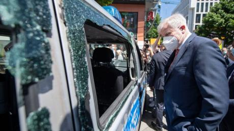 Bundesinnenminister Horst Seehofer betrachtet nach der Krawallnacht von Stuttgart ein beschädigtes Polizeiauto.
