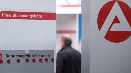 Ein Mann im Wartebereich hinter einer Stellwand für Stellenangebote in Stuttgart.