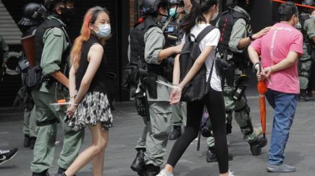 Polizisten führen Demonstranten mit am Rücken zusammengebundenen Händen ab.