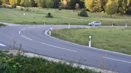 Die Kreisstraße mit ihrer scharfen Kurve am Riesrand bei Großsorheim ist ein beliebter Treffpunkt für Motorradfahrer und Autofahrer, die dort ständig auf und ab fahren, während sich die Zuschauer auf dem Parkplatz versammeln.