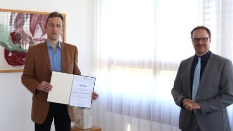 Der neue Kreisarchäologe Stefan Reuter mit der Ernennungsurkunde und Landrat Thorsten Freudenberger.