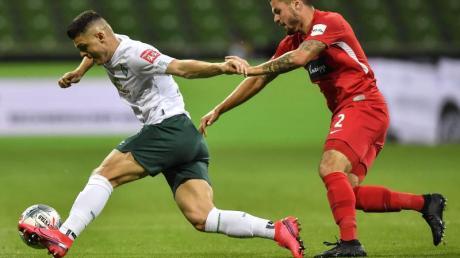Werder-Profi Milot Rashica (l) wird vom Heidenheimer Marnon Busch verfolgt.